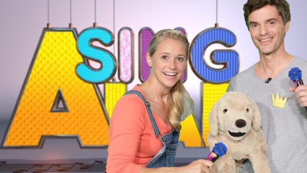 Singa steht neben einem Mann, der einen Stofftierhund auf dem Arm hat. | Rechte: ZDF