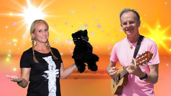 SingAlarm: Moderatorin Singa mit Willy Astor im SingAlarm Studio. Singa hat den Katerstrophen-Kater in der Hand und Willy Astor seine Gitarre. | Rechte: MES