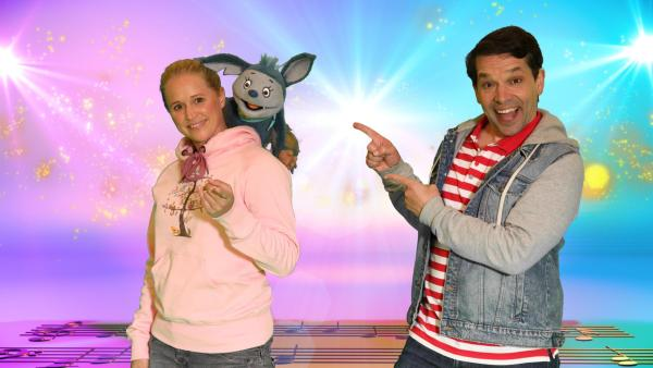 Moderatorin Singa zeigt mit dem Finger in die Kamera und lacht, Handpuppe Fidi, die Fledermaus, sitzt auf ihrer Schulter. Studiogast Juri zeigt mit zwei Fingern auf Singa und lacht in die Kamera.   Rechte: ZDF