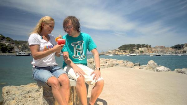 Singa und herrH sitzen auf einem Stein einer Hafenpromenade. Singa, die ein weißes SingAlarm-Shirt und eine kurze Jeans trägt, hält einen roten Cocktail in der Hand. Ihr Urlaubsgast herrH, der ein türkises herrH-Shirt und eine weiße Hose trägt, sieht auf den Cocktail. | Rechte: ZDF/Nicolas Omonsky