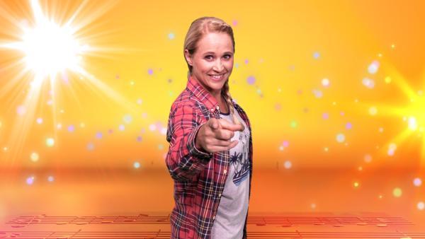 Singa steht vor einem orangenen Hintergrund und zeigt mit ihrem rechten Zeigefinger geradeaus | Rechte: ZDF