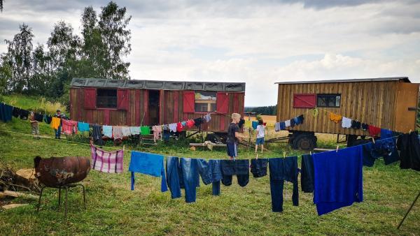 Alles selber gemacht. Die klitschnassen Sachen tropfen im Sommerwind. Ben und Juri begutachten sie. | Rechte: MDR/Cine Impuls Leipzig