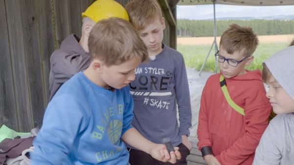 Gespannt schauen die anderen Jungs Alvin beim Devilstickbauen über die Schulter. | Rechte: MDR/Cine Impuls Leipzig