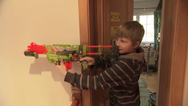 Matej ist mit einem Spielzeuggewehr auf Verfolgungsjagd nach seinem Bruder. | Rechte: ZDF/Filip Majer