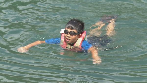 Kenshi, der ein Muscheltaucher werden möchte, muss zunächst schwimmen lernen. Mit großer Angst und Schwimmweste wagt er sich ins Wasser.   Rechte: ZDF/Toru Suzuki