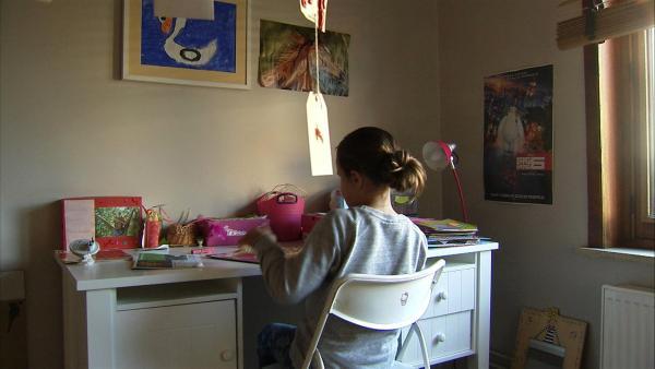 Anna sitzt in ihrem Zimmer am Schreibtisch und macht Hausaufgaben. Sie ist entschlossen: der Alltag soll weitergehen. | Rechte: ZDF/Kristiaan Grauwels