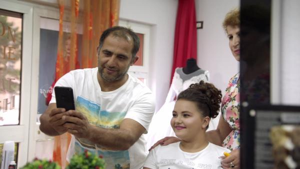 Fetijes Vater ist stolz auf seine schöne und kluge Tochter. Fetije sitzt geschminkt und frisch frisiert im Salon und lächelt, dabei schaut sie in das Handy ihres Vaters, der neben ihr steht und ein Foto von ihr macht. | Rechte: ZDF/Sven Vleugels