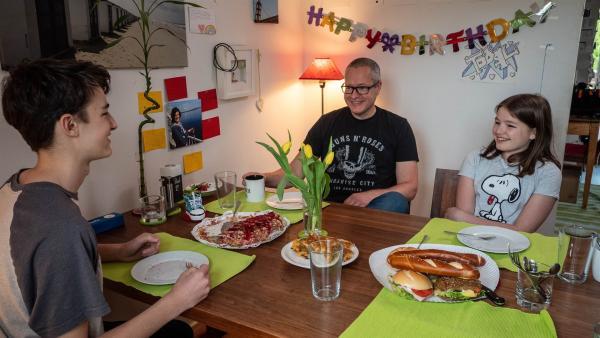 Jule frühstückt mit ihrem Vater und ihrem Bruder. Heute erzählt sie ihnen von ihrem geplanten Projekt für die Krebshilfe. | Rechte: ZDF/Florian Lippke