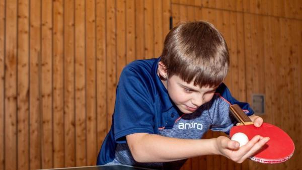 Adrian trainiert den Aufschlag. Er schaut konzentriert auf den Ball, den er kurz vor dem Schläger in die Luft wirft. Er trägt ein blaues T-Shirt, hat kurze mittelblonde Haare und steht vor einer Holzwand. | Rechte: ZDF