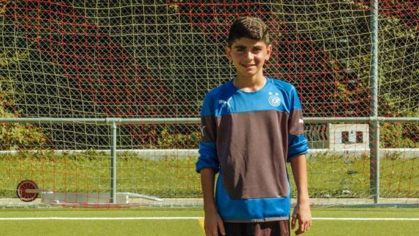 Ayham steht auf dem Fußballplatz vor dem Tor. Er trägt ein blau/schwarzes Trikot und schaut freundlich in die Kamera. Die Sonne scheint. | Rechte: ZDF