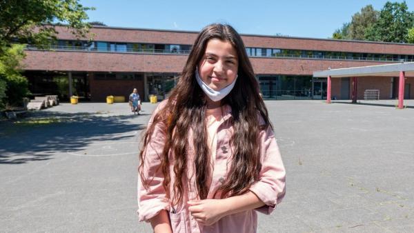 Azra steht mit heruntergezogener Maske vor dem Schulgebäude. Azra hat langes dunkles Haar, trägt eine Jeans und eine rosafarbene Jacke. Der Schulhof hinter ihr ist leer. Sie lacht in die Kamera. | Rechte: ZDF