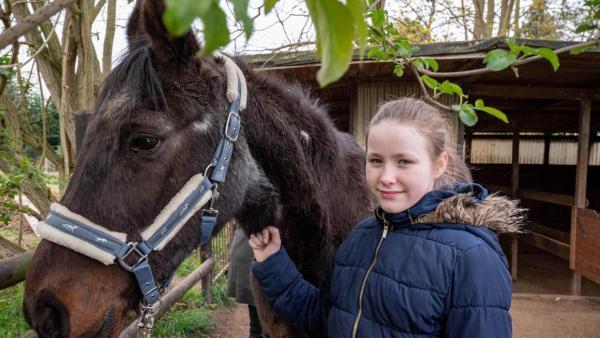 Evi steht mit ihrem alten Pferd Foxi vor dem Stall. Evi hat eine blaue Jacke an mit Fellkragen. Ihr blondes langes Haar hat sie zu einem Zopf gebunden. Sie lacht in die Kamera. Mit der rechten Hand hält sie ihre Pferd Foxi am Halfter. | Rechte: ZDF