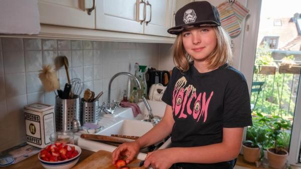 Jakub hat schulterlanges, blondes Haar und eine schwarze Kappe auf. Er steht in der Küche an einem großen Holzschneidebrett und schneidet Erdbeeren. Neben ihm steht eine große Schüssel mit bereits geschnittenen Erdbeeren. Er schaut in die Kamera und lächelt. | Rechte: ZDF