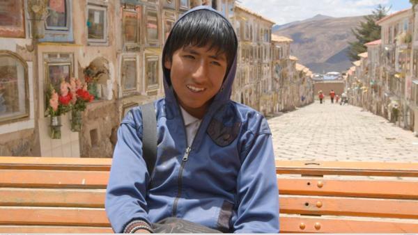 Portrait von Juan-Carlos. Er sitzt auf einer Holzbank und trägt eine blaue Kapuzen-Jacke. Er lacht in die Kamera.   Rechte: ZDF