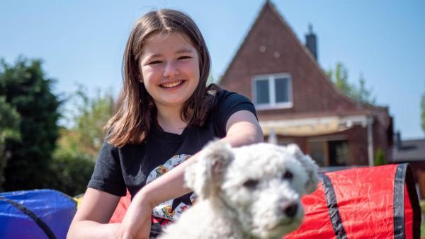 Jule hockt mit dem weißen Hund Bounty auf der Wiese und lächelt in die Kamera. Die Sonne scheint. Es sind Tunnel im Hintergrund zu sehen, durch die der Hund laufen soll.   Rechte: ZDF