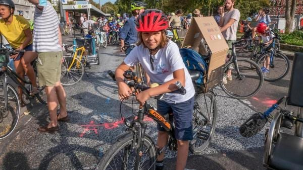 Jupp trägt einen roten Fahrradhelm und steht an seinem Rad mitten unter vielen Radaktivisten bei der Fahrraddemo. Er trägt ein weißes T-Shirt mit Aufschrift.  Die Sonne scheint. Jupp lächelt in die Kamera. | Rechte: ZDF