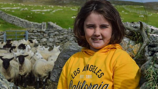 Lena lächelt freundlich in die Kamera. Sie hat halblange, dunkle Haare und trägt einen knallgelben Hoodie. Sie steht in einem Schafsgatter, das von Steinen begrenzt ist. Neben ihr drängen sich etliche Schafe zusammen. Im Hintergrund kann man schottische Weidelandschaft erkennen. | Rechte: ZDF
