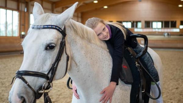 Lenya liegt gemütlich auf dem Rücken ihres Pferdes und lächelt in die Kamera. Dabei umarmt sie ihren Schimmel, Santana, liebevoll. Lenya trägt ihr langes, blondes Haar zum Zopf. Die Reithalle im Hintergrund ist leer.   Rechte: ZDF