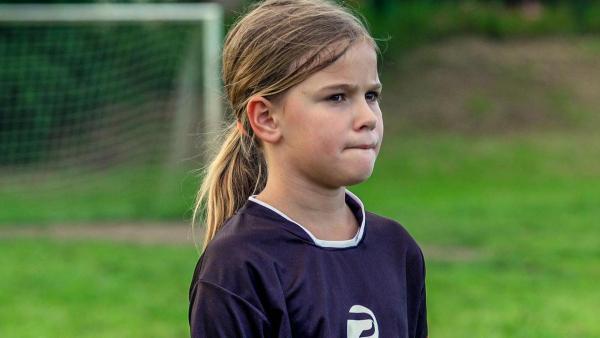 Porträt von Luana. Luana trägt ein Fußball-Trikot und befindet sich auf dem Fußballplatz.  Sie beißt sich auf die Unterlippe und wirkt sehr konzentriert. Im Hintergrund steht ein Fußballtor.   Rechte: ZDF