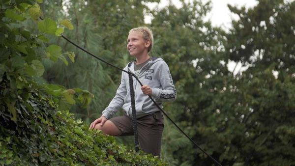 Luka steigt lächelnd einen dicht mit Efeu bewachsenen Hügel hoch. Mit einer Hand hat er ein Sicherungsseil umfasst. Luka hat blondes, kurz geschnittenes Haar, trägt Shorts und eine graue Kapuzenjacke. Er sieht sehr glücklich aus. | Rechte: ZDF