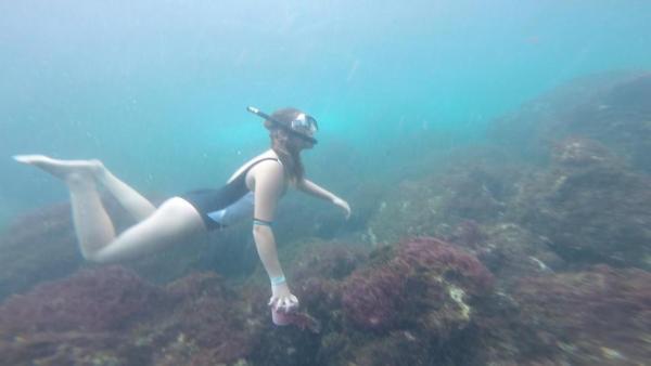 Maria taucht im Meer. Sie trägt einen Badeanzug, eine Taucherbrille und einen Schnorchel. Sie schwimmt über ein Korallenriff. In der Hand hält sie Plastikmüll, den sie gerade vom Boden aufgesammelt hat.   Rechte: ZDF