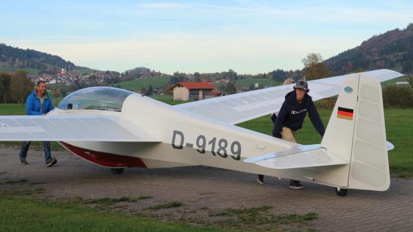 Marius bringt zusammen mit seinem Fluglehrer seinen Flieger zur Startbahn. Sein Trainer schiebt den vordereren Teil des Flugzeugs, während Marius das Heck anschiebt. Im Hintergrund ist eine Berglandschaft zu sehen.   Rechte: ZDF