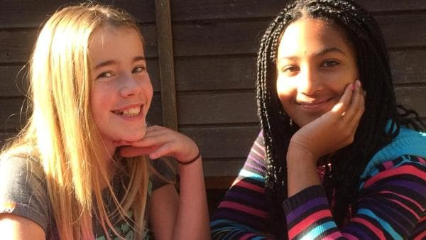 Pauline sitzt mit ihrer Freundin Angélique an einem Gartentisch in der Sonne. Beide lachen in die Kamera.   Rechte: ZDF