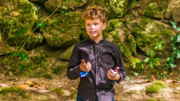Tiago steht vor einer moosbewachsenen Felswand im Wald. Hier will er seine erste Unterrichtsstunde halten. Er trägt eine Jeans und ein dunkles Hemd und wirkt konzentriert und zuversichtlich.   Rechte: ZDF