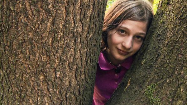 Yael schaut zwischen zwei riesigen Baumstämmen in die Kamera. | Rechte: ZDF
