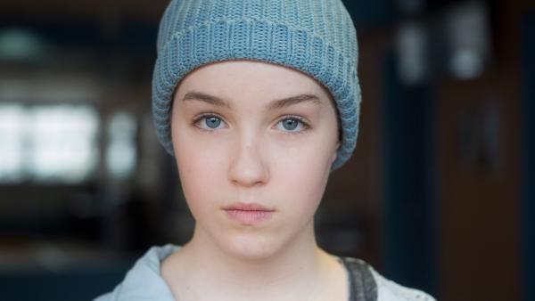 Jenny ernst mit Mütze in einer dunklen Halle. | Rechte: KiKA/Productions Avenida 2017, Sébastien Raymond