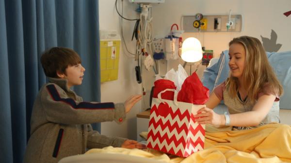 Jennys Bruder Felix (William Coallier) ist zum ersten Mal bei Jenny (Émilie Bierre) zu Besuch im Krankenhaus. Er hat ein Geschenk dabei. | Rechte: KiKA/Productions Avenida 2017, Sébastien Raymond