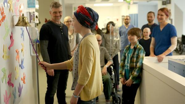 Diejenigen, die das Krankenhaus verlassen können, läuten vor allen die Glocke. Für Jenny (Émilie Bierre) ist es soweit und alle freuen sich mit ihr.  | Rechte: KiKA/Productions Avenida 2017, Sébastien Raymond