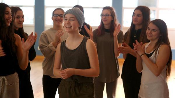 Die Tanzgruppe applaudiert Jenny (Émilie Bierre). | Rechte: KiKA/Productions Avenida 2017, Sébastien Raymond