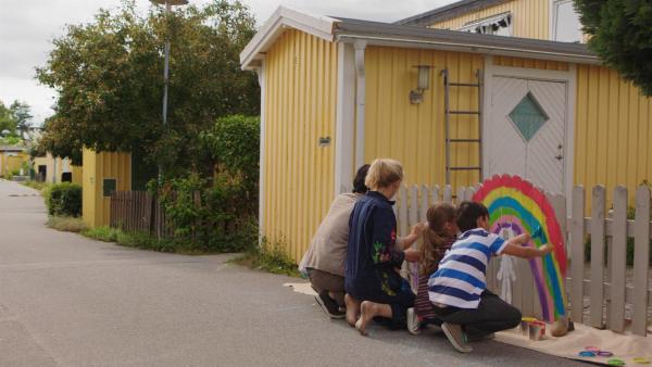 Klara (Paulina Pizarro Swartling) malt mit Mama und Papa einen Regenbogen an den Zaun. | Rechte: KiKA/Erik Vallsten