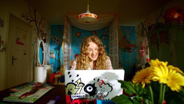 Lea (Katharina Wolfert) ist happy. Finn ist jetzt online mit ihr befreundet. | Rechte: KiKA/FEEDMEE
