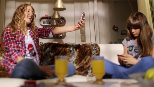 Endlich! Lea (Katharina Wolfert, li.) bewundert ihr nagelneues Handy, während Nelli (Fanni Pantförder) ihres im Dauereinsatz hat. | Rechte: KI.KA/Timm Lange