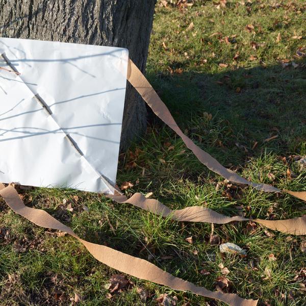 fertiger Drachen liegt an einem Baum gelehnt auf einer Wiese | Rechte: KiKA