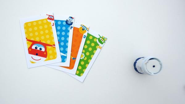 Falte die Karten in der Mitte und klebe sie zusammen. Die Vorderseite der Karten ist bunt und du siehst darauf eine Figur. Die Rückseite ist hellblau mit blauen Punkten. | Rechte: KiKA