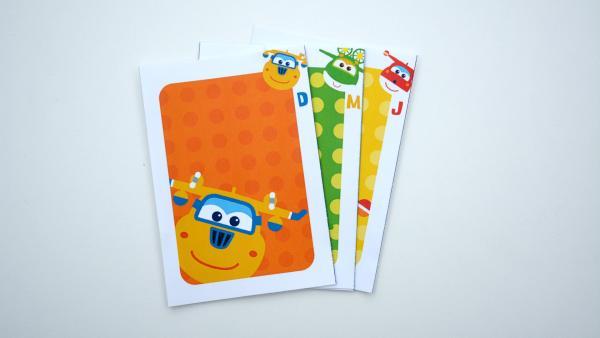 Nun schiebst du eine Karte mit der Vorderseite nach oben vorsichtig unter die umgeklappte, aufgeklebte Kartenecke. Die letzte Karte legst du leicht schräg darüber. Es sieht aus, als hättest du nur drei Karten vor dir liegen. <br/><br/>Jetzt kannst du den Kartentrick vorführen. Du solltest vorher üben damit er auch wirklich funktioniert. | Rechte: KiKA