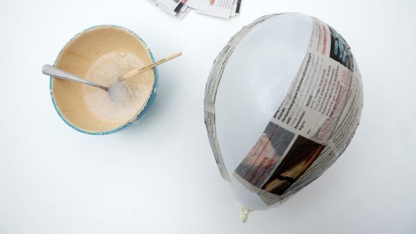 eine Schüssel  mit angerührtem Tapetnkleister, daneben ein Luftballon mit einigen aufgeklebten Zeitungsstreifen | Rechte: KiKA