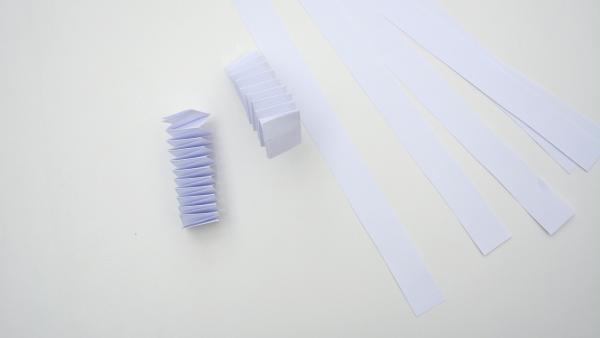 Papierstreifen und zwei aus Papierstreifen gefaltete Hexentreppen | Rechte: KiKA