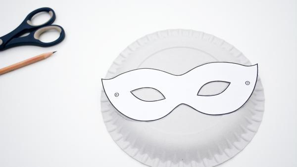 ausgeschnittene Maske liegt auf einem Pappteller | Rechte: KiKA