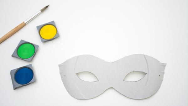 ausgeschnittene Maske, Wasserfarben und Pinsel | Rechte: KiKA