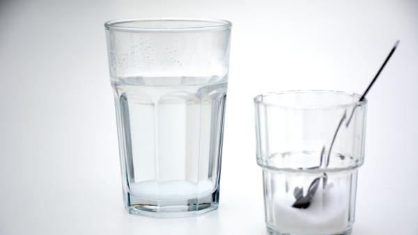 Glas mit heißem Wasser und Salz sowie Glas mit Salz und Löffel | Rechte: KiKA