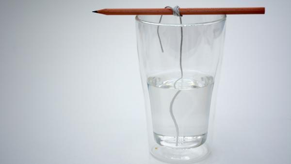 Glas mit Wasser, auf dem ein Bleistift mit Baumwollfaden liegt | Rechte: KiKA
