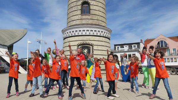 Singa zeigt Volker in Warnemünde, wie schön es an der Ostsee ist. Der lässt sich von den Leuchttürmen zu einem Leuchtturm-Lied inspirieren, den alle zusammen singen und tanzen. | Rechte: Franziska Rülke/ZDF/KiKA