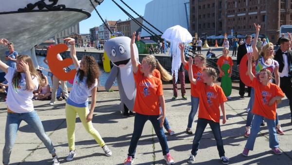 Vor dem Ozeaneum in Stralsund warten schon viele Besucher, um mit dem Tanzalarm AEIOU zu tanzen. | Rechte: Franziska Rülke/ZDF/KiKA