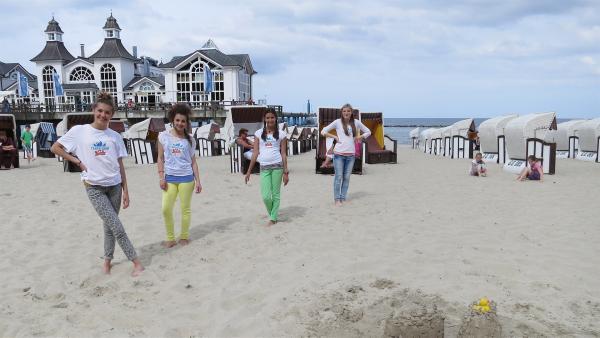 Am Strand von Sellin träumen die TanzalarmKids von einem Schloss am Meer, bevor alle gemeinsam auf der Seebrücke mit den Urlaubern zu AEIOU tanzen. | Rechte: KiKA/ZDF/Franziska Rülke