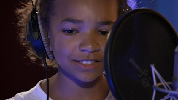 Eine spannende Zeit beginnt für die vier neuen TanzAlarm-Kids. Sie sind das erste Mal in einem Tonstudio, um an dem Mikrofon ihre eigenen Songs aufzunehmen. Hannah hat zum Glück schon Erfahrung im Singen. | Rechte: KiKA/MingaMedia