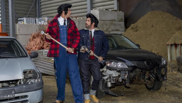 Zwei Männer hämmern abwechselnd im Takt auf ein Autowrack ein. | Rechte: KiKA/MingaMedia/Holger Kast